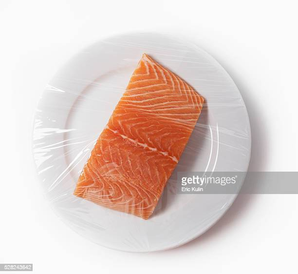 salmon on a plate with plastic wrap - plastic plate stock photos and pictures