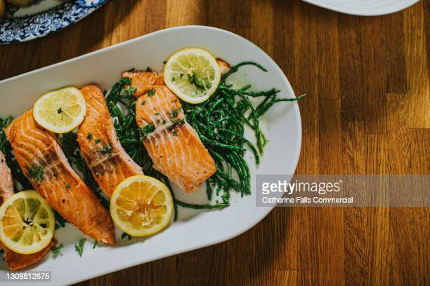 salmon on a serving plate on a table - table stock pictures, royalty-free photos & images