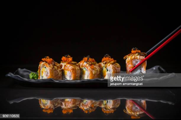 salmon roll topped caviar and foie gras - sushi restaurant stock photos and pictures