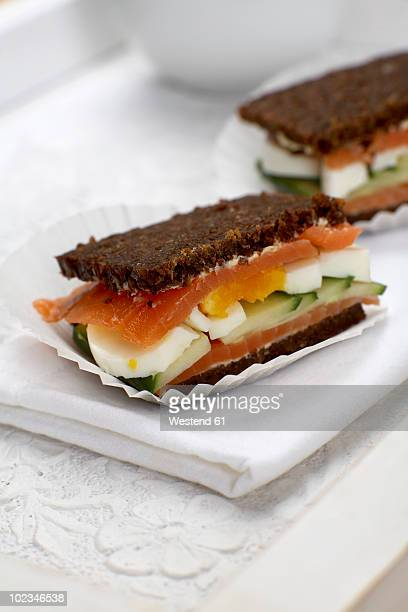 Salmon sandwich with egg and cucumber, close-up
