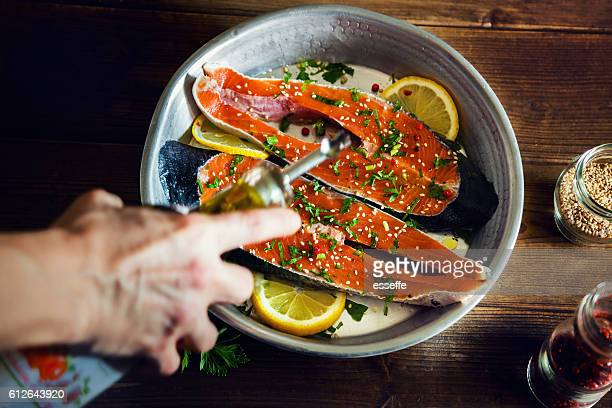 salmon slices seasoned with lemon, sesame oil and parsley - food state stock pictures, royalty-free photos & images