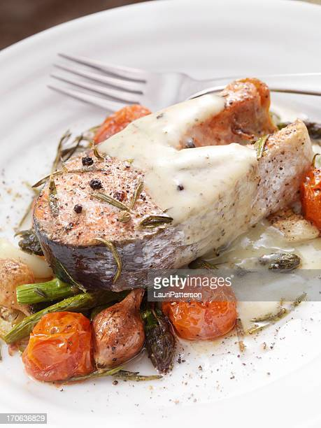salmon steak on roasted vegetables - bechamel sauce stock photos and pictures