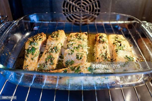 salmon steaks being cooked on an oven - peterselie stockfoto's en -beelden