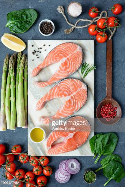 Salmon steaks, spices, herbs, olive oil and vegetables. Healthy cooking background