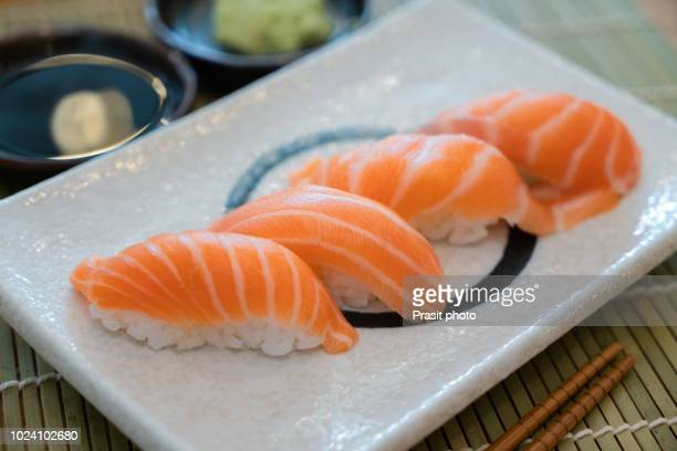 salmon sushi on white plate along with japanese sauce and wazabi. japanese restaurant. - nigiri stock pictures, royalty-free photos & images