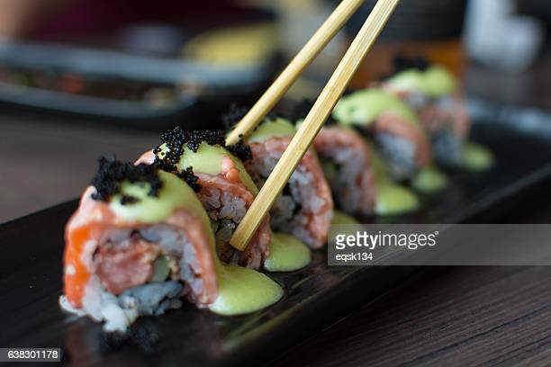 salmon sushi with chopsticks - sushi stock pictures, royalty-free photos & images