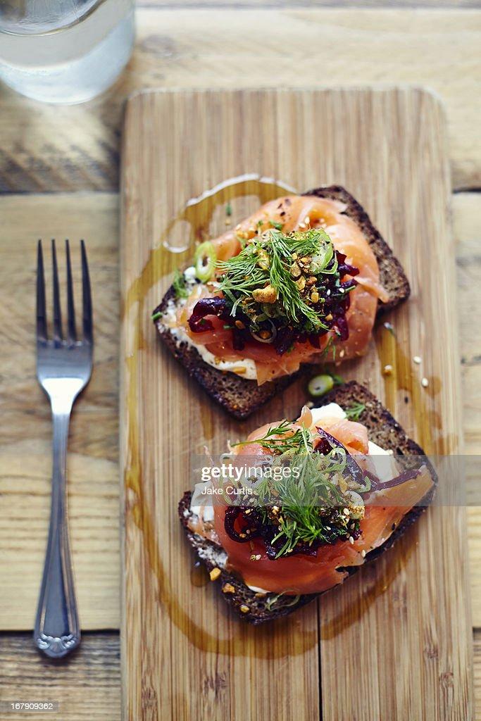 salmon tartine on rye bread on wooden board : Stock Photo