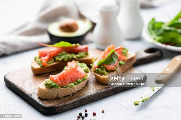 salmon toast with avocado healthy snack or appetizer - avocado toast stockfoto's en -beelden