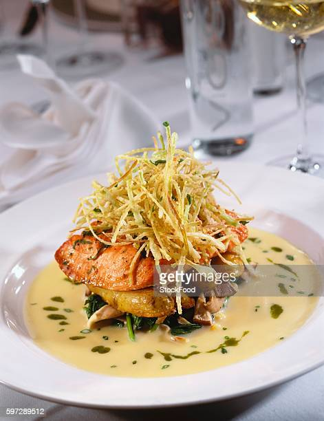 Salmon with leek straw on potatoes, spinach and mushrooms