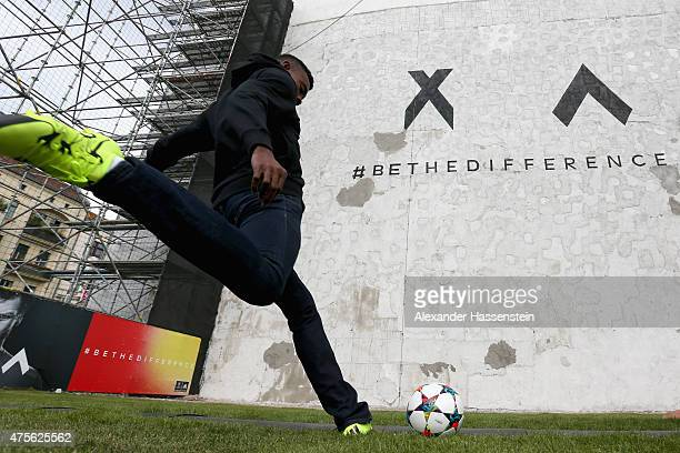 Salomon Kalou kicks a ball to unveil artwork hidden by a wall on June 2, 2015 in Berlin, Germany.