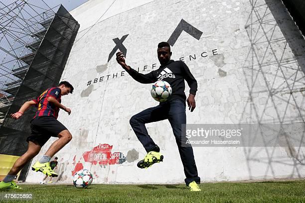Salomon Kalou kicks a ball to unveil artwork hidden by a wall on June 2, 2015 in Berlin, Germany.