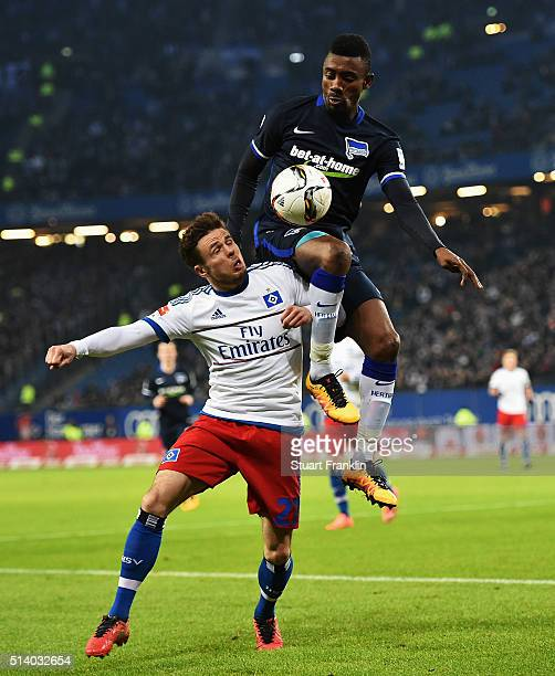 Salomon Kalou of Berlin is challenged by Nicolai Müller of Hamburg during the Bundesliga match between Hamburger SV and Hertha BSC at...