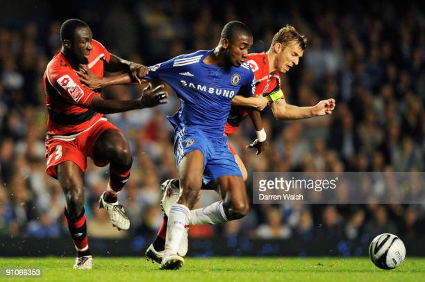Salomon Kalou of Chelsea is held back by Jay Simpson and Martin Rowlands of QPR during the Carling Cup third round match between Chelsea and Queens...