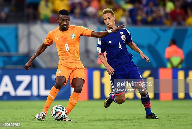 Salomon Kalou of the Ivory Coast comes under pressure from Keisuke Honda of Japan during the 2014 FIFA World Cup Brazil Group C match between Cote...