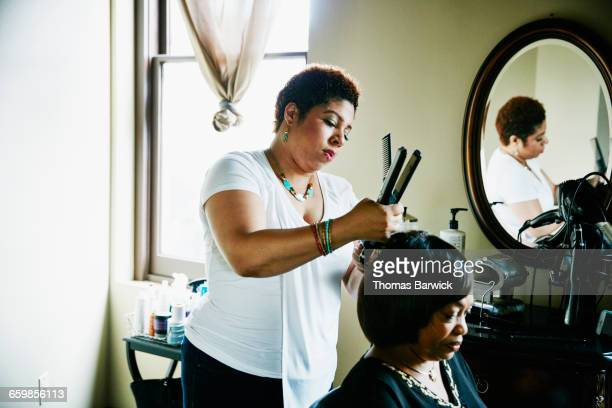 salon owner straightening hair of client in salon - black hair stock pictures, royalty-free photos & images