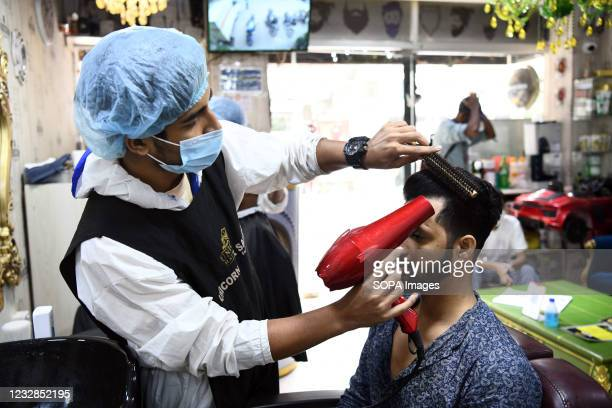 Salon staff wearing personal protective equipment as a preventive measure against the spread of COVID19 works on a client in salon.