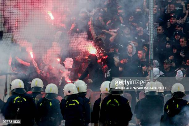 Salonika's fans throw flares towards police officers ahead of the Greek Cup Final football match between AEK FC and PAOK Salonika at the Olympic...