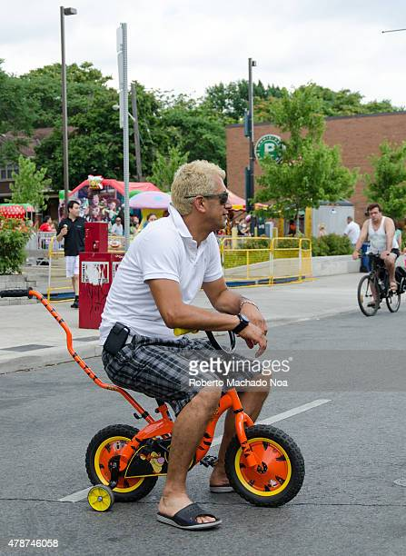 WEST TORONTO ONTARIO CANADA Salsa on St Saint Clair Festival Scenes A blond man riding a miniature bicycle with training wheels seems unaware of how...
