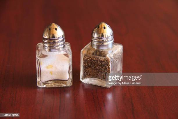 salt and pepper shaker on table - salt and pepper shakers stock pictures, royalty-free photos & images