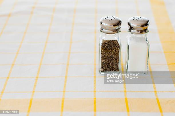Salt and pepper shakers on checked tablecloth