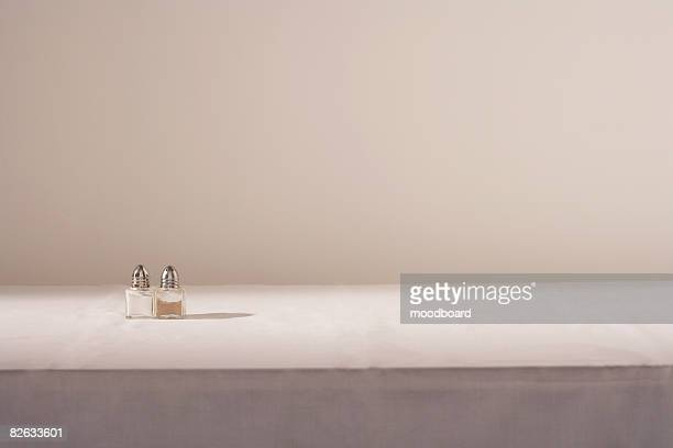 salt and pepper shakers on table - salt and pepper shakers stock pictures, royalty-free photos & images