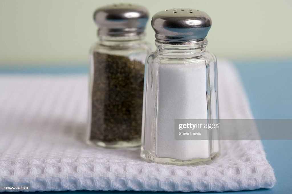 Salt and pepper shakers on tea towel, close-up : Stock Photo