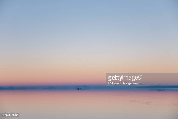 salt flat at sunrise, salar de uyuni, bolivia - horizon over land stock photos and pictures