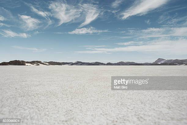 salt flat landscape with blue sky and mountains