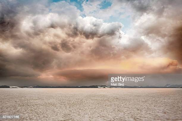 salt flat landscape with stormy sky and mountains
