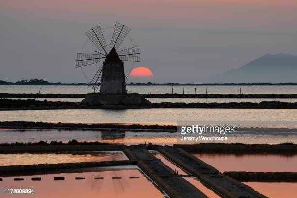 salt flats and windmill at sunset - jeremy woodhouse stock pictures, royalty-free photos & images