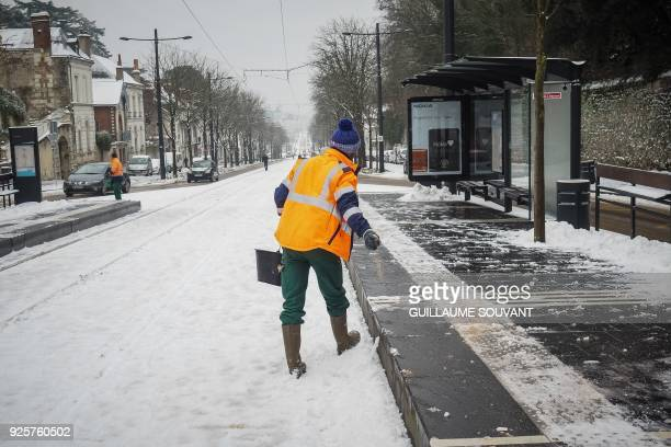 Salt is thrown on the sidewalk after snowfall in Tours on March 1 2018 Fresh heavy snowfalls and icy blizzards were expected to lash Europe on March...