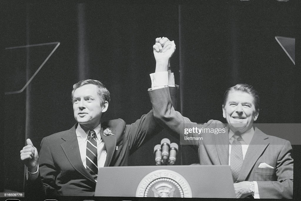 President Ronald Reagan, (R), raises his arm with Utah Sen. Orrin Hatch during a Republican rally here (10/28). Sen. Hatch gives the crowded arena the thumbs up signal, hopeful the President's visit will boost his chances for reelections in November.