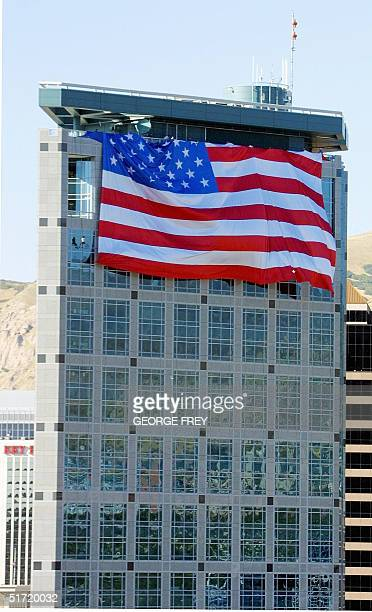 Salt Lake Olympic Committee workers unfold a 180' x 127' American flag on top of the SLOC 24 storey building in downtown Salt Lake City Utah 19...