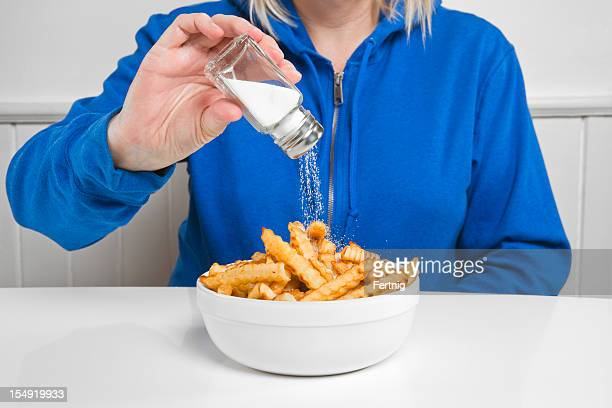 salt on french fries - sodium stock photos and pictures
