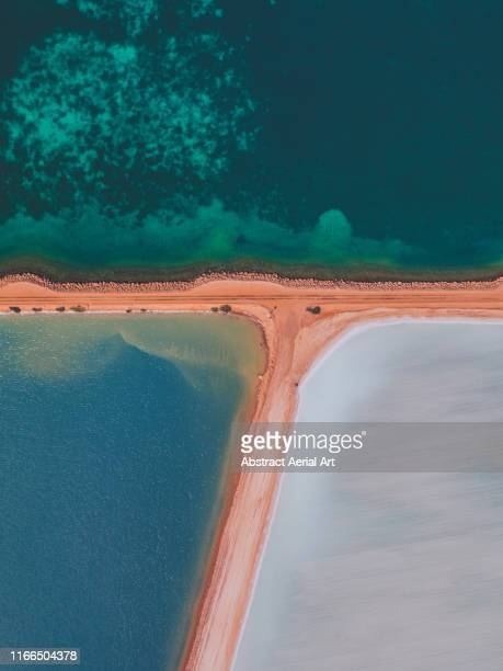 salt storage ponds by the ocean as seen from above, western australia - ソルトポンド ストックフォトと画像
