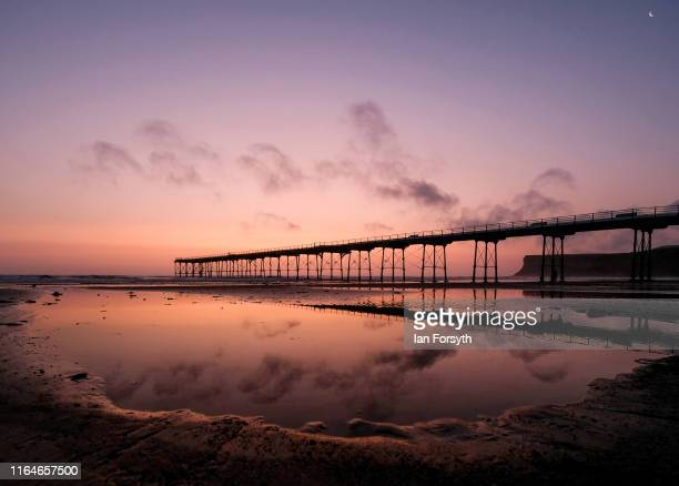 Saltburn pier is reflected in a pool of seawater at sunrise on July 28 2019 in SaltburnByTheSea England The weekend has seen milder temperatures...