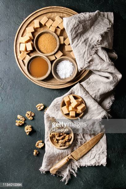Salted caramel fudge candy served on wooden board with fleur de sel caramel sauce brown cane sugar and caramelized walnuts in wood bowls over black...