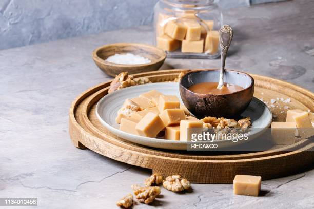 Salted caramel fudge candy served on wooden board with fleur de sel caramel sauce and caramelized walnuts in bowls over grey kitchen table Dessert set