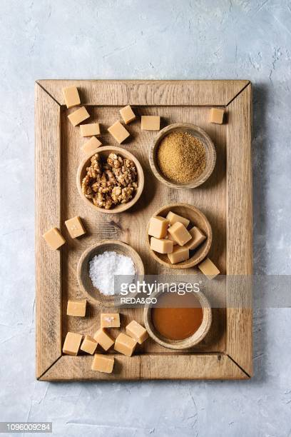 Salted caramel fudge candy served on wooden tray with fleur de sel caramel sauce brown cane sugar and caramelized walnuts in wood bowls over grey...