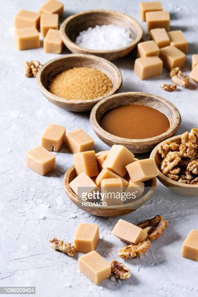 Salted caramel fudge candy served with fleur de sel caramel sauce brown cane sugar and caramelized walnuts in wood bowls over grey texture background...