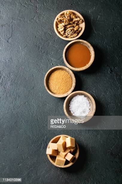 Salted caramel fudge candy served with fleur de sel caramel sauce brown cane sugar and caramelized walnuts in wood bowls over black texture...