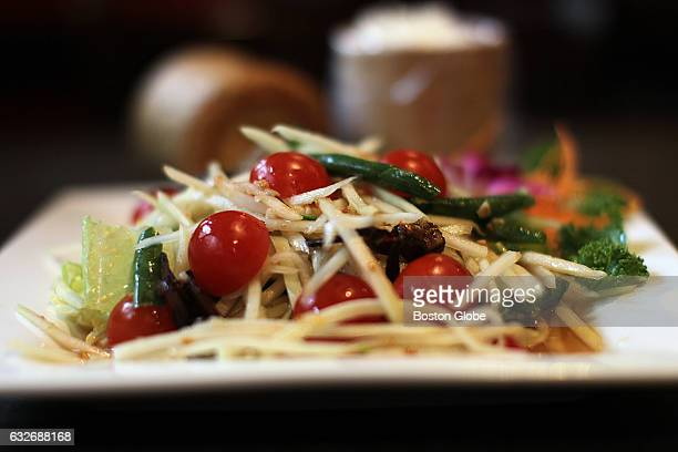 Salted crab papaya salad with bamboo canister of sticky rice is pictured at Montien in Boston on Feb 16 2016