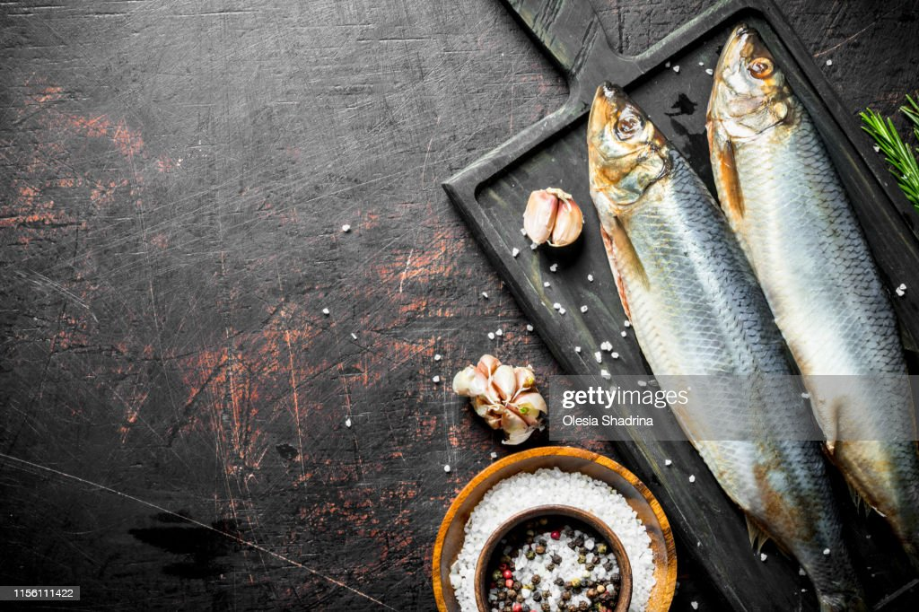 Salted herring with garlic cloves and spices in bowl. : Stock Photo
