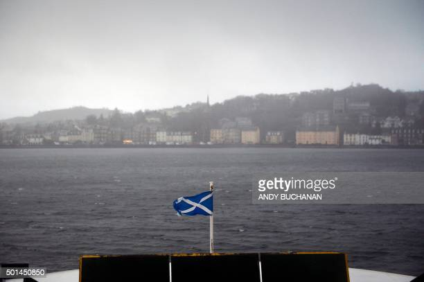 Saltire flag the national flag of Scotland flies from the prow of a ferry as it approaches the town of Rothesay on the Isle Of Bute an island off of...