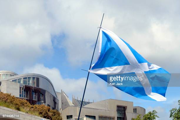 Saltire is flown aloft in front of the Scottish Parliament by one of the hundreds of independence supporters taking part in a pro-independence...