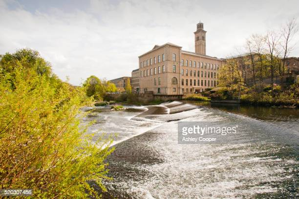 salts mill in saltaire, yorkshire, uk and a weir on the river aire. - philanthropist stock pictures, royalty-free photos & images