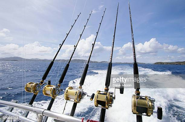 saltwater fishing rods affixed to boat's stern - big game fishing stock photos and pictures