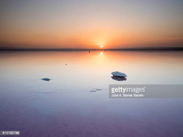 Saltwater lake with salt formations, in a sunset with water reflections orange