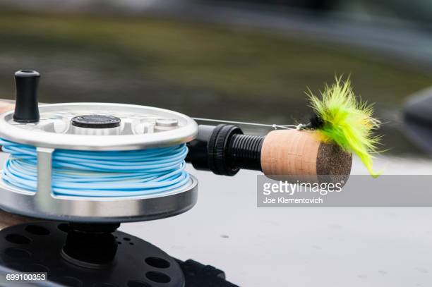 Saltwater reel, rod and fly sitting on top of a car ready for fly fishing.