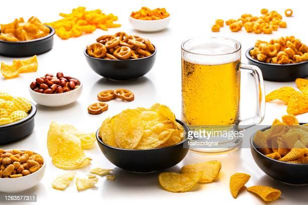 白い背景に分離された塩辛いスナックとビール - 塩味スナック ストックフォトと画像